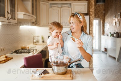 Mother with her daughter mixing melted chocolate