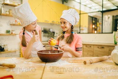 Little girls cooks in caps sniffing vanilla powder