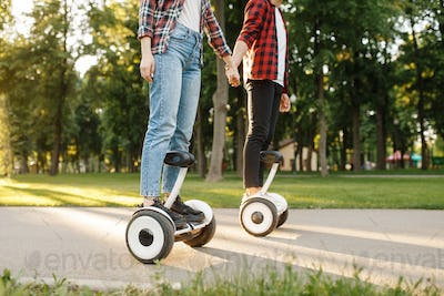 Young couple riding on gyroboard in park at sunset
