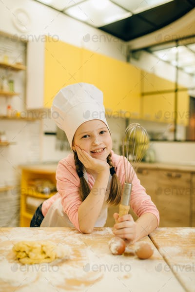 Little girl cook in cap and apron on the kitchen