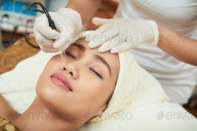 Undergoing Darsonvalization on Facial Skin