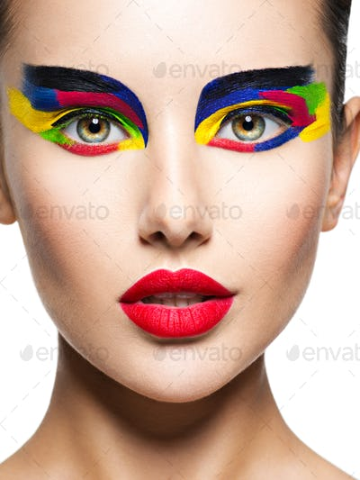 Beautiful Face of a woman with multicolors vivid make-up of eyes
