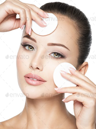 Beautiful woman cleans the face with  cotton swab.