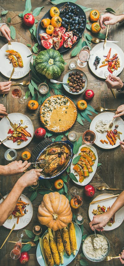 Friends feasting at Thanksgiving Day table with turkey, narrow composition