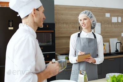 Frowning woman discussing menu with chef