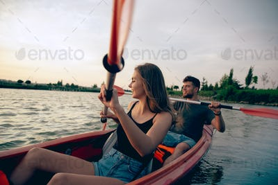 Confident young couple kayaking on river together with sunset on the background