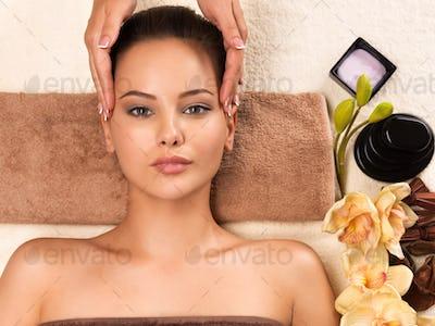 Beautiful woman getting head massage in the spa salon.