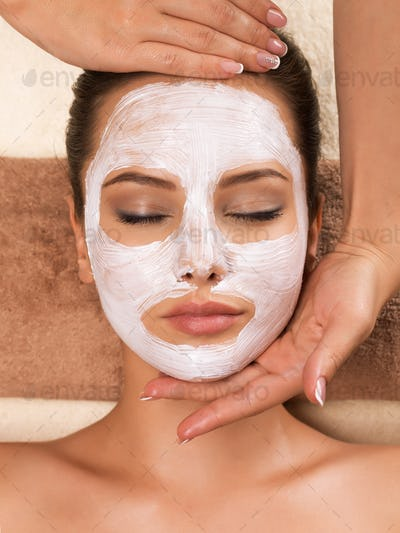 Woman with mask on her face having head massage.