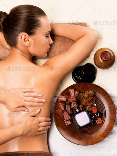 Beautiful woman relaxing and getting back massage.
