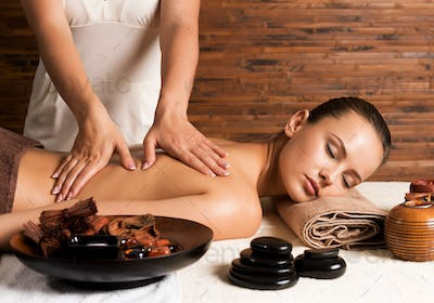 Woman with closed eyes having massage of body.