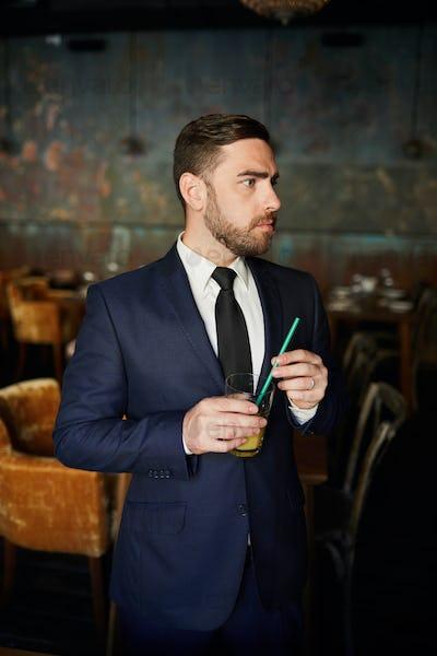 Worried businessman drinking juice