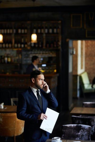 Restaurant manager talking on mobile phone