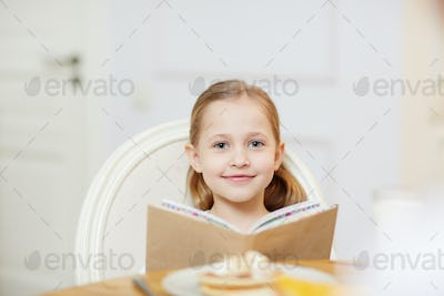 Smiling girl reading book in kitchen