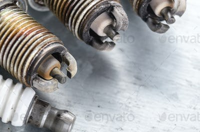 New and used spark plugs for internal combustion engine on metal
