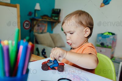 Toddler boy playing alone in his room with a toy motorbike