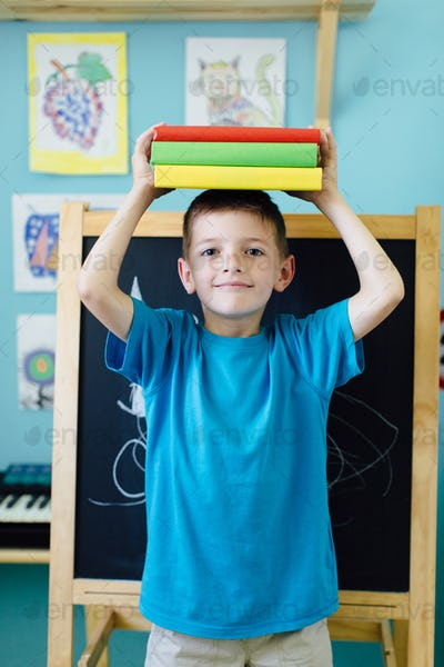 Smiling schoolboy balancing books on his head