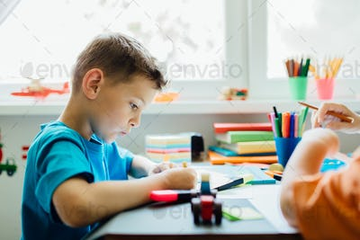 Side view of a whistling student doing his homework