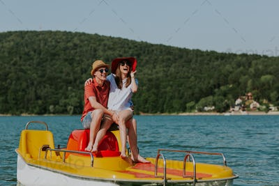 Couple in love laughing while boating in the lake.