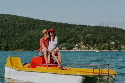 Young lovers having fun in pedalo boat on hot summer day.