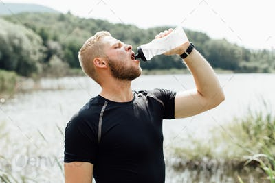 Side view of a thirsty male runner drinking water at a pond