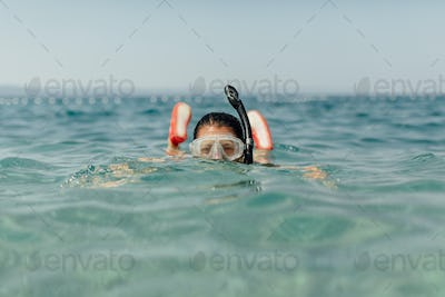 Woman wearing diving mask and snorkel swimming in sea.