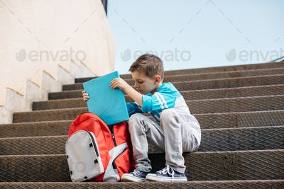 Young school boy sitting outside a school and taking a book out from bag