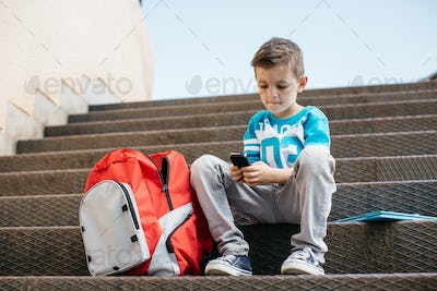 Schoolboy taking a break from school and browsing his mobile