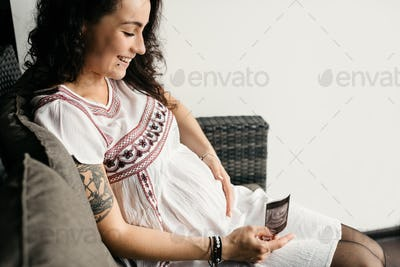 Portrait of a happy pregnant woman touching her belly and looking at a scan of her baby.