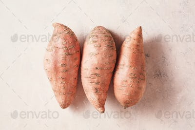 Three large sweet potatoes on a textured pink background