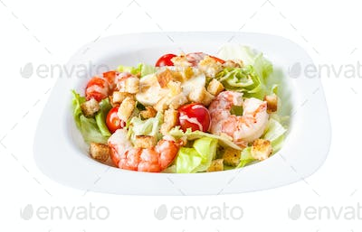 Caesar salad with prawns on white plate isolated