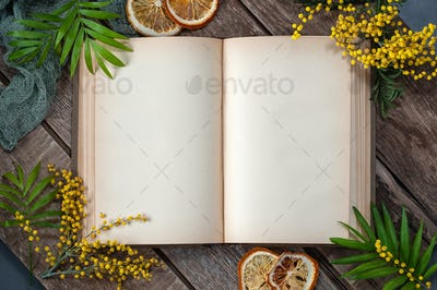 An old open book with blank pages on an old wooden table in a sp