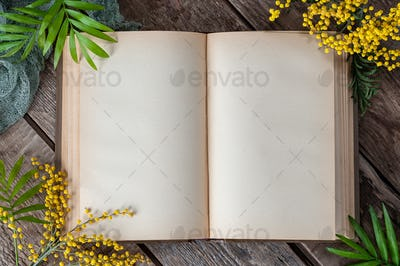 Opened book with blank pages on old wooden table. Background ima