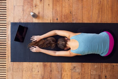 Overhead View Of Woman Stretching On Exercise Mat Using Digital Tablet