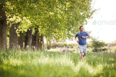 Man Exercising Running Through Countryside Field