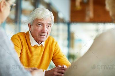 Serious senior man talking to colleagues