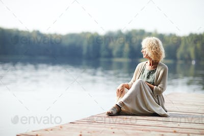 Pensive mature lady on pier