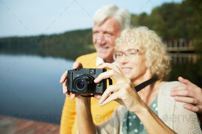 Senior couple photographing nature on vacation