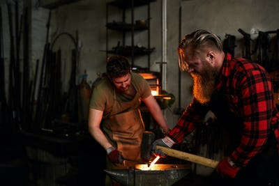 Blacksmiths shaping metal together
