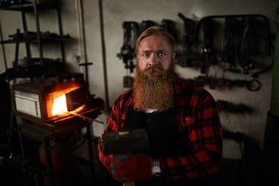 Long bearded metalsmith in workshop