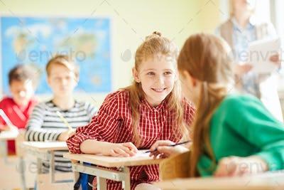 Positive classmates talking at lesson