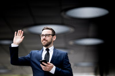 Business man with smartphone showing hello sign