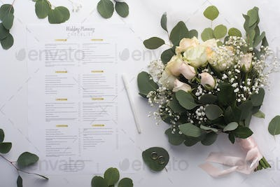 Bridal roses bouquet and planning checklist on white