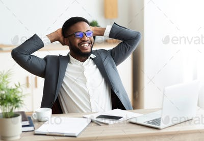 Young african american businessman relaxing at workplace in modern office