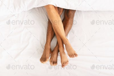 Male and female legs under duvet lying on bed