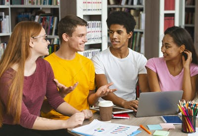 Young college students studying together at library