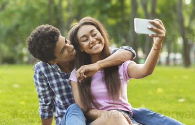 Capturing happy moments. Two cheerful teenagers making selfie outdoors