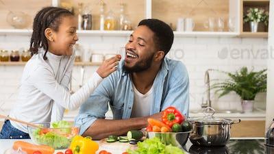 Lovely afro girl giving her dad tomato to taste