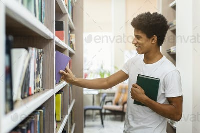 African american young guy choosing books at campus library