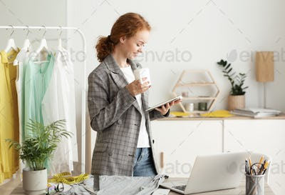 Coffee break. Fashion designer drinking coffee and using tablet