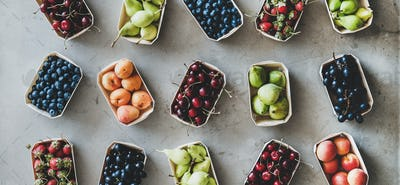 Various fruits and berries over grey concrete background, wide composition